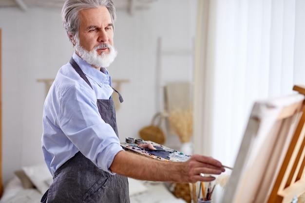 Künstler, der das schaffen des meisterwerks unter verwendung des pinsels hält, stehen nahe leinwand, grauhaariger mann in der schürze genießen zeichnen
