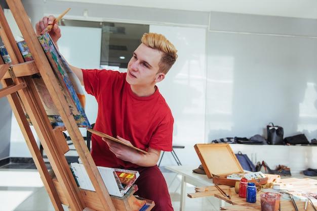 Künstler, der ein bild in einem studio malt