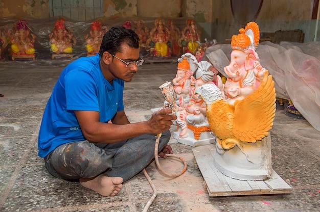 Künstler, der eine statue herstellt und einem idol des hinduistischen gottes lord ganesha in einer künstlerwerkstatt für das ganesha-fest den letzten schliff gibt.