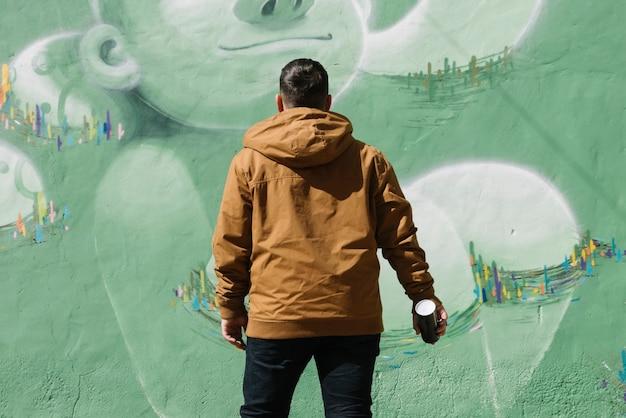Künstler, der in der hand vor graffitiwand mit aerosoldose steht
