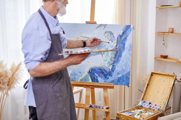 Künstler, der in die schaffung von kunst eingetaucht ist und leinwand auf staffelei malt. handwerker in schürze genießen das malen