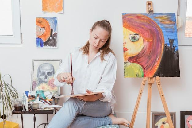 Künstler, der pinsel in der farbe auf palette eintaucht
