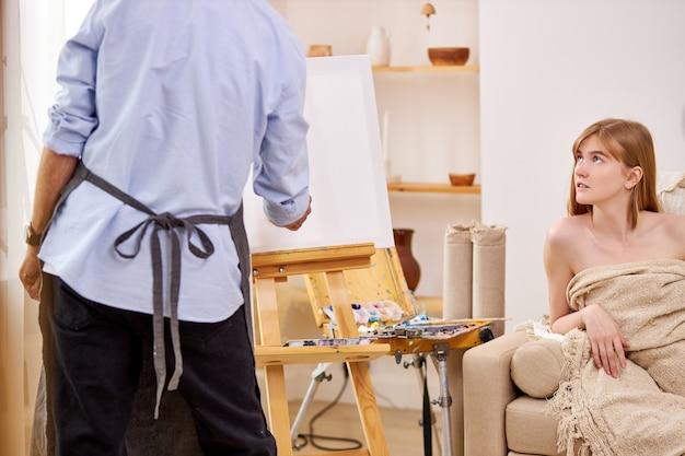 Künstler, der porträt des weiblichen modells auf leinwand zeichnet, junge kaukasische dame sitzt auf couch, die für kunst aufwirft