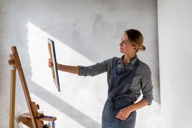 Künstler, der segeltuch im studio betrachtet