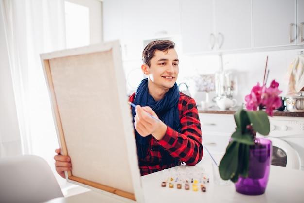 Künstler des jungen mannes, der zu hause kreative malerei malt