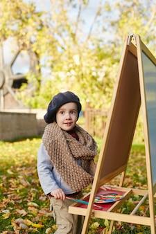 Künstler des kleinen jungen zeichnet farben auf leinwandstaffelei