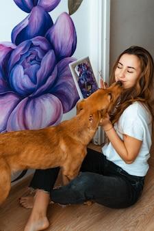 Künstler. designer. haustiere. junge mädchenkünstler malt an einer wand drinnen. arbeitet und spielt mit einem hund. haustiertherapie. innenarchitektur. der kreative prozess.