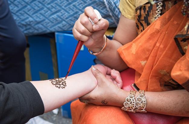 Künstler, die henna-tätowierung auf frauenhänden anwenden. mehndi ist traditionelle indische dekorative kunst.