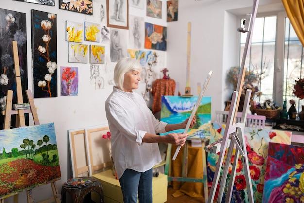 Künstler fühlen sich inspiriert. talentierte reife schöne künstlerin, die sich wirklich inspiriert fühlt, wenn sie ihr bild betrachtet