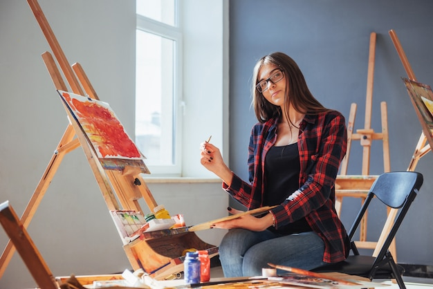 Künstler hält einen pinsel in der hand und zeichnet ein bild auf leinwand