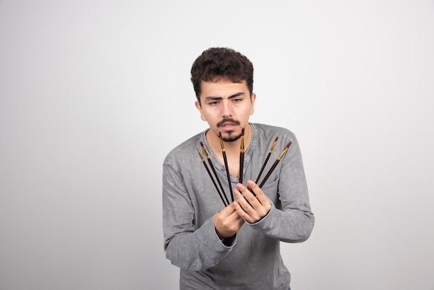 Künstler hält seinen neuen satz professioneller malpinsel.