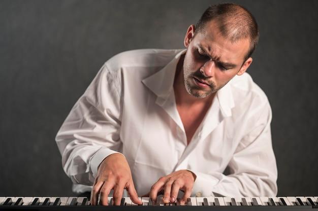 Künstler im weißen hemd, das tastaturen betrachtet