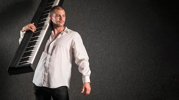 Künstler im weißen hemd, das tastaturkopienraum hält