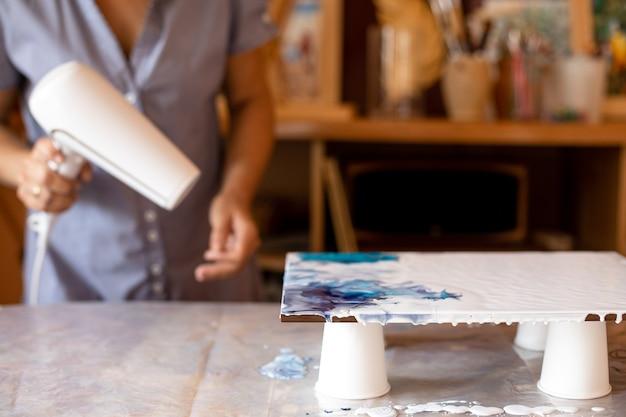 Künstler macht bild auf tisch in ihrem studio. sie mischt farben, indem sie sie mit einem fön bläst. innenanstrich. kreativität und gestaltung. hobbys und handwerk. freiheit und kreativität. lebensstil.