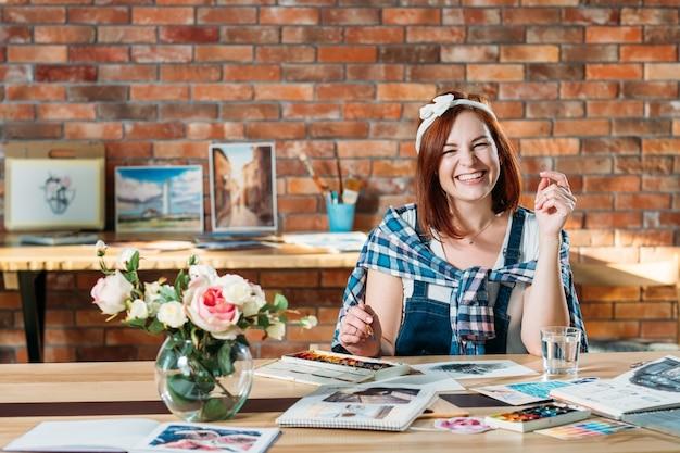 Künstler malerei freude. lächelnde rothaarige frau, die aquarellbild tut. skizzenbuch und palettenzubehör herum.