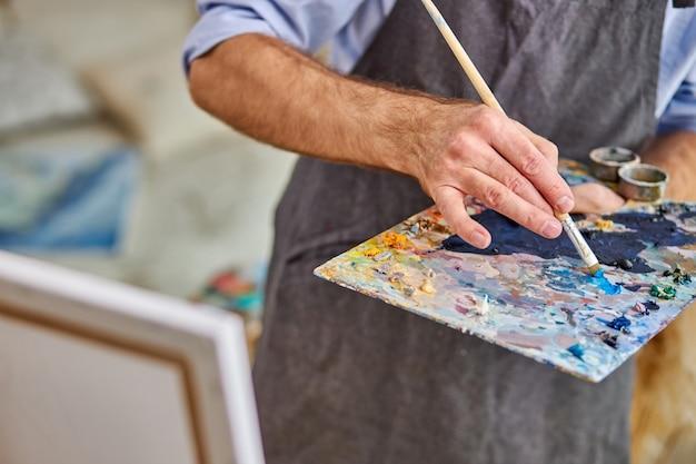 Künstler mischen farben auf palette halten in der hand nah oben. kreativität, kunstkonzept