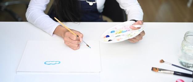 Künstler mit einer palette in den händen, die auf papier im wohnzimmer malen