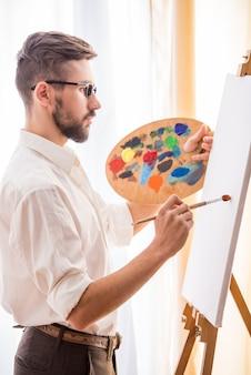 Künstler mit pinsel und palette wird ein bild malen