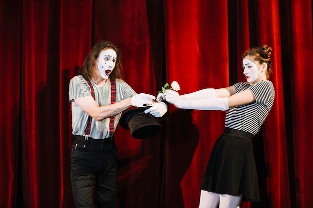 Künstler mit zwei pantomimen, der am stadium vor rotem vorhang durchführt