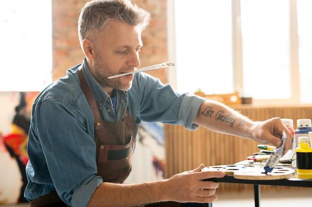 Künstler mittleren alters mit pinsel im mund, der am tisch in der werkstatt sitzt und blaue ölfarbe von der röhre auf palette drückt