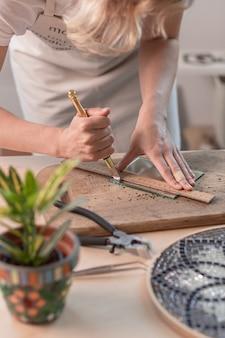 Künstler schneidet buntglasplatten in kleine mosaikquadrate. nahaufnahme