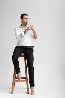 Künstler sitzt auf stuhl und spielt flöte