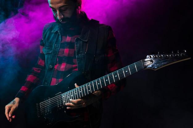 Künstler spielt gitarre und violettes bühnenlicht und rauch