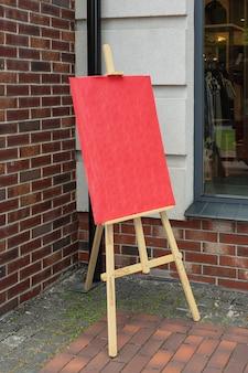 Künstler-staffelei aus holz mit rotem leerem mockup-poster für ihr design vor backsteinmauer