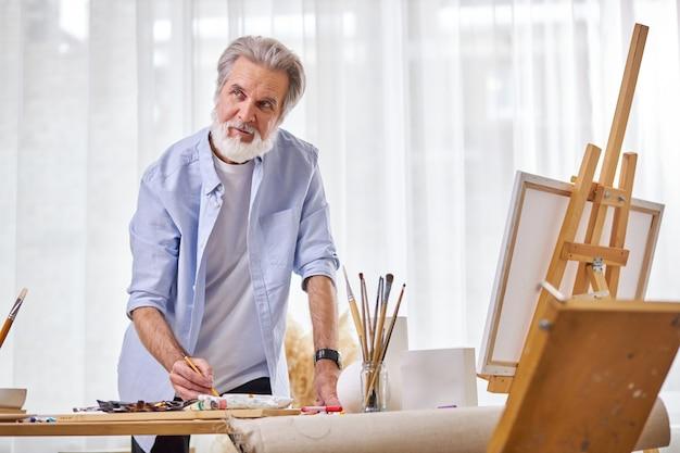 Künstler während der arbeit, in kontemplation stehen, beim zeichnen denken, werkzeuge zum malen verwenden