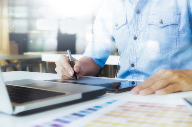 Künstler zeichnung auf grafische tablette mit farbmustern im büro. architektonische zeichnung mit werkzeugen und zubehör.