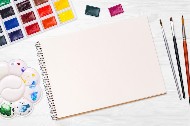 Künstlerarbeitsplatz. album, farben, palette und pinsel auf einem weißen hölzernen hintergrund.