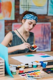 Künstlerarbeitsplatz. junge malerin, die abstrakte kunstwerke im studio schafft