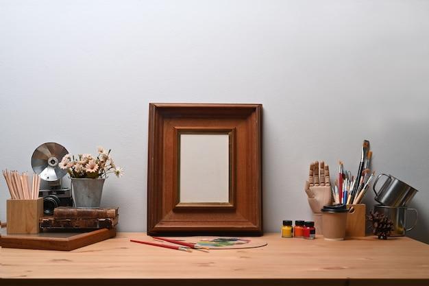 Künstlerarbeitsplatz mit leerem bilderrahmen, kamera und malwerkzeugen auf holztisch.