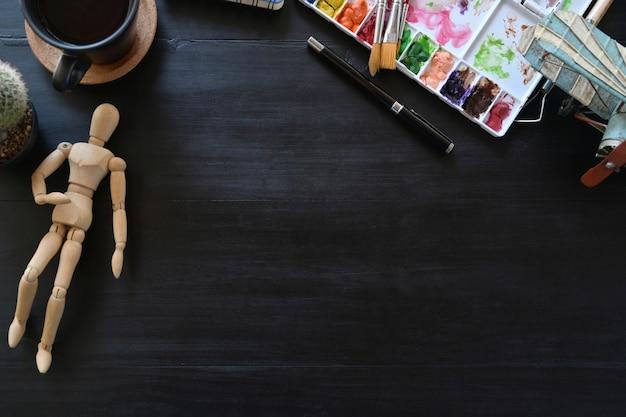 Künstlerarbeitsplatzfarbe mit kreativem zubehör auf dunkler hölzerner tabelle. arbeitsbereich und textfreiraum.