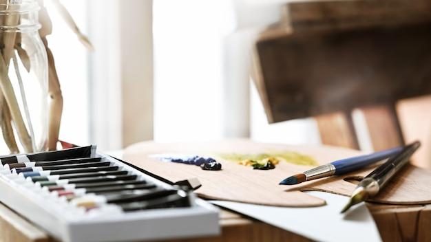 Künstlerausrüstung, die auf hölzernen arbeitstisch setzt.