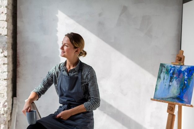 Künstlerfrau, die auf stuhl mit gestell und malerei aufwirft