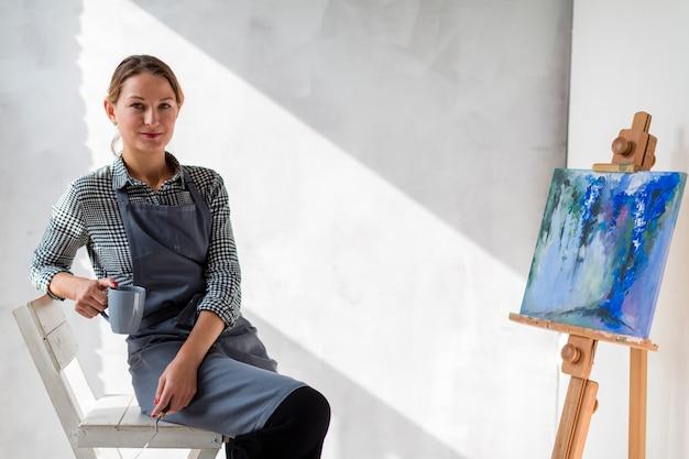 Künstlerfrau, die auf stuhl mit malerei aufwirft