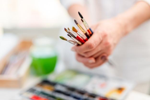 Künstlerfrau, die in ihren händen verschiedene größen und farbenpinsel hält. nahaufnahme