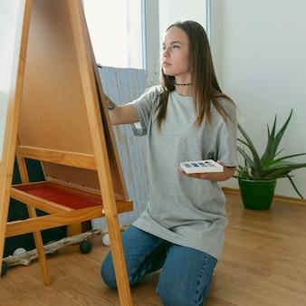 Künstlerfrau malt auf leinwand seitenansicht