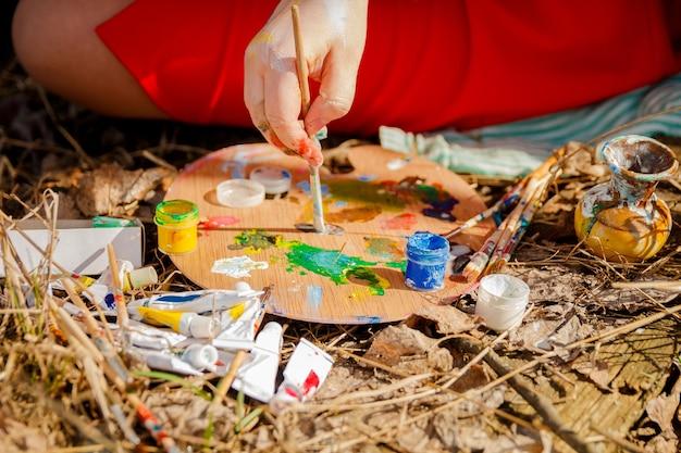 Künstlerhand, die das bild und die palette mit farben und pinseln auf grashintergrund zeichnet.