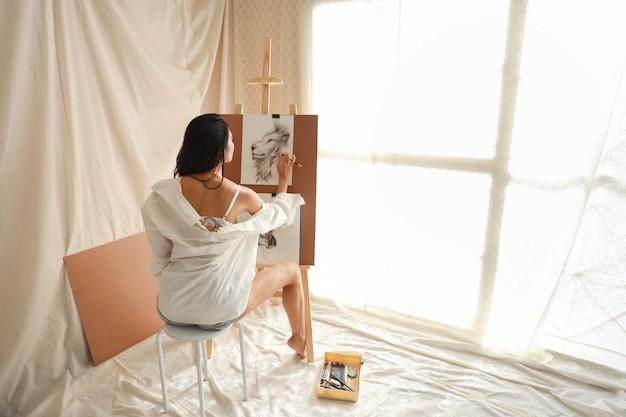 Künstlerin der hinteren ansicht im weißen hemd, das bild mit bleistift zeichnet (frauenlebensstilkonzept)
