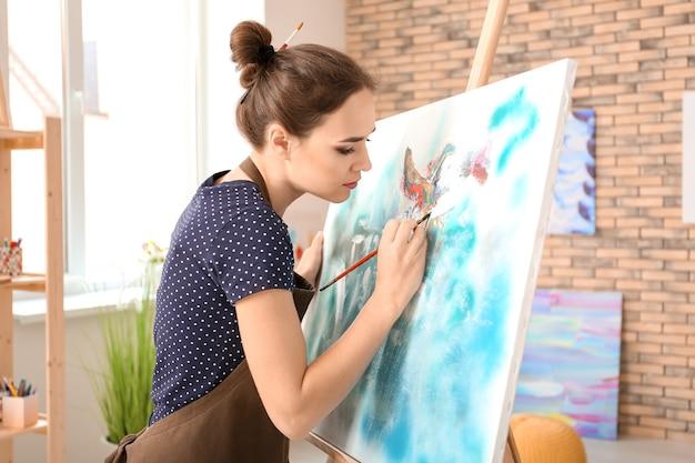 Künstlerin, die bild in der werkstatt malt