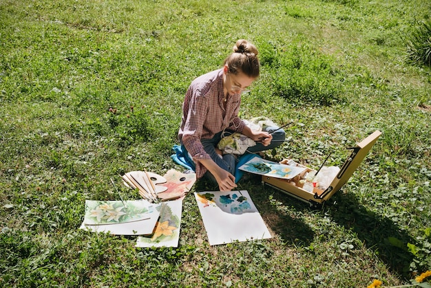 Künstlerin, die blumen mit öl malt im freien, maler zeichnet