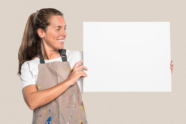 Künstlerin, die eine weiße leinwand mit designfläche zeigt