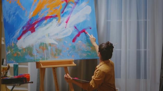 Künstlerin, die in ihrem atelier arbeitet und eine leinwand mit verschiedenen farben malt.