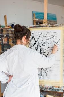 Künstlerin, die kreativ auf leinwand mit holzkohle zeichnet