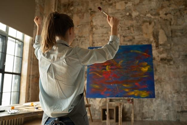 Künstlerin freut sich am ende der arbeit und hebt die hände