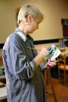 Künstlerin malerin konzentriert und inspiriert malerei mit pinsel und ölfarben auf leinwand