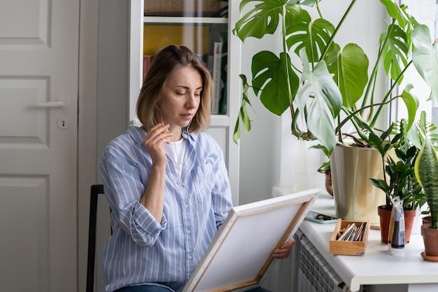 Künstlerin malt ein bild auf leinwand, spricht über kopfhörer, macht eine pause und sitzt am fenster