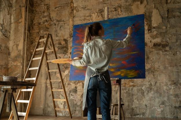 Künstlerin malt ein bild ihres ateliers in ihren händen sind pinsel und eine palette
